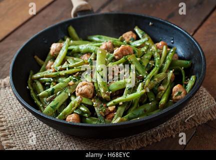 Haricots verts avec des boulettes de poulet frit à l'ail et de style asiatique. Banque D'Images