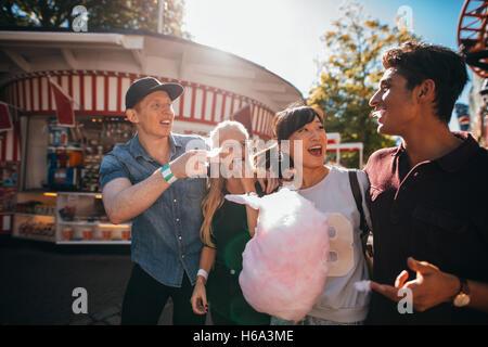 Groupe d'amis s'amuser tout en mangeant la barbe à des expositions. Jeune homme et femmes avec candyfloss au parc Banque D'Images