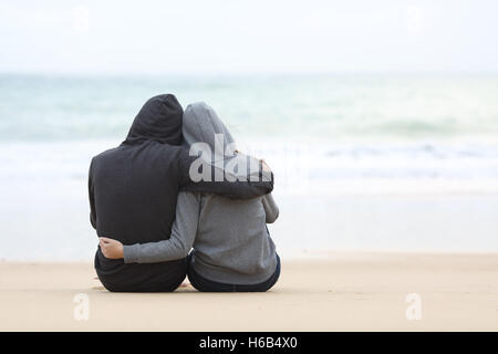 Vue arrière d'un couple d'adolescents pensif hugging et regarder la mer assis sur le sable de la plage, dans un Banque D'Images