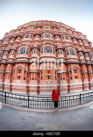 Femme en robe rouge avec écharpe debout près de façade de Hawa Mahal, Rajasthan, Inde Banque D'Images