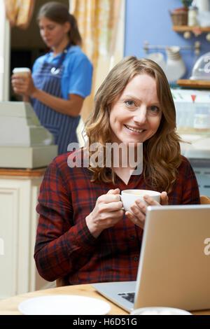 Femme dans un café à l'aide d'un ordinateur portable
