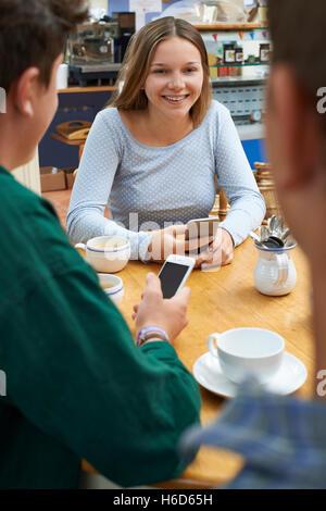 Groupe d'amis adolescents réunion dans un café et l'utilisation de téléphones mobiles Banque D'Images