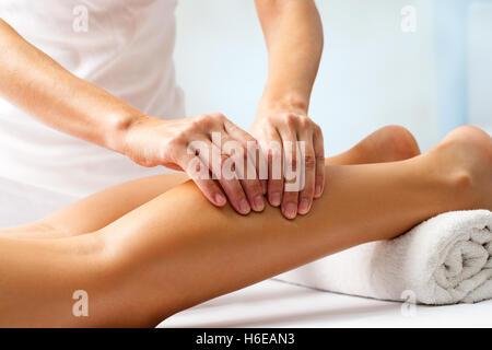 Détail des mains humaines massage musculaire au mollet.Thérapeute exerçant une pression sur la jambe féminine. Banque D'Images