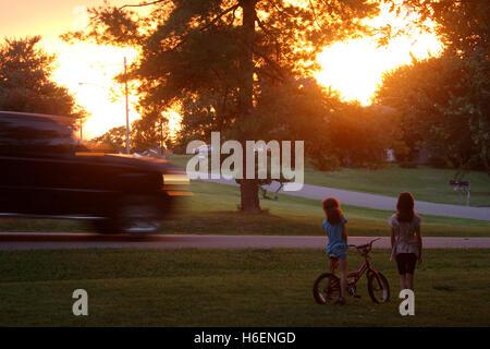 Deux jeunes filles debout regardant le coucher du soleil dans la cour Banque D'Images