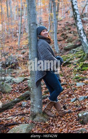 Une femme glamour de la randonnée à travers les bois en automne automne vêtu d'un poncho en laine décontracté usure loisirs woolly hat gloves