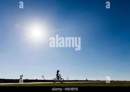 Silhouette d'un enfant à vélo passant sur un sentier du parc sur une claire journée d'été, soleil de l'après-midi. Banque D'Images