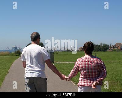 Couple d'âge moyen marche main dans la main le long du front de mer vers Weston Rockfield, Southampton, Hampshire, Banque D'Images