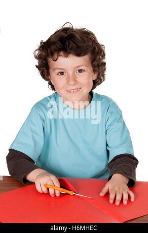 Enfant faisant de l'artisanat avec du carton et des ciseaux isolé sur fond blanc Banque D'Images