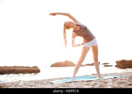 Belle jeune femme mains étirement au cours de yoga sur la plage