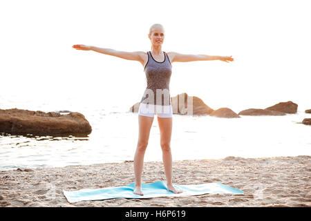Belle jeune femme faisant des exercices d'étirement au cours de yoga sur la plage