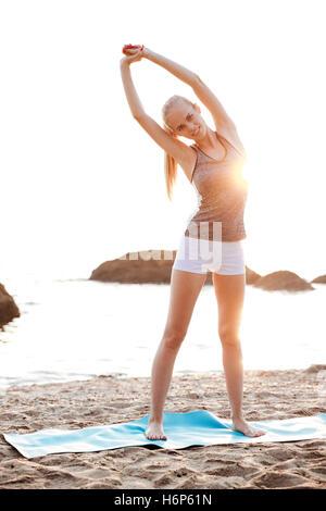 Happy smiling woman doing stretching au cours des exercices de yoga sur la plage