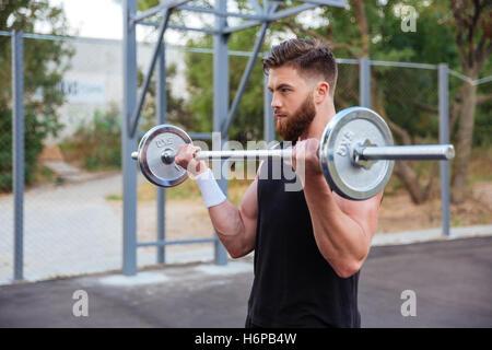 Homme barbu beau musculaire entraînement avec haltères longs à l'extérieur Banque D'Images