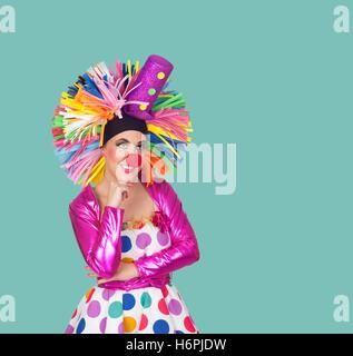 Jeune fille rêveuse clown avec une grosse perruque colorés sur fond vert Banque D'Images