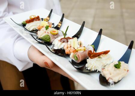 Détail de waiter holding canapes sur cuillères en plastique. Banque D'Images