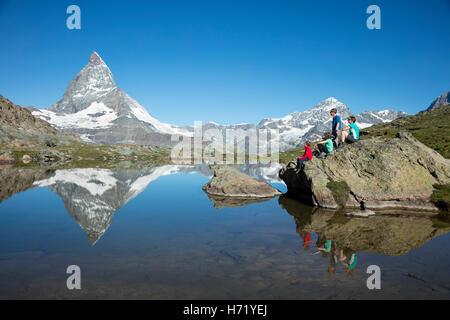 Randonnées famille et Cervin reflète dans l'. Riffelsee Alpes valaisannes, Zermatt, Valais, Suisse. Banque D'Images