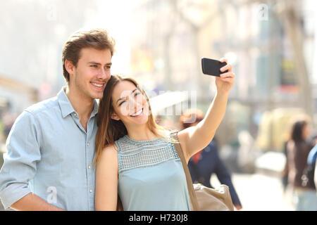 Couple de touristes photographier une rue d'une ville en selfies Banque D'Images