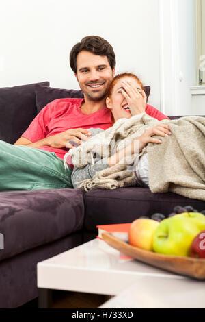 Les jeunes amoureux couple dans le salon sur le canapé tout en regardant la télévision et lecture Banque D'Images