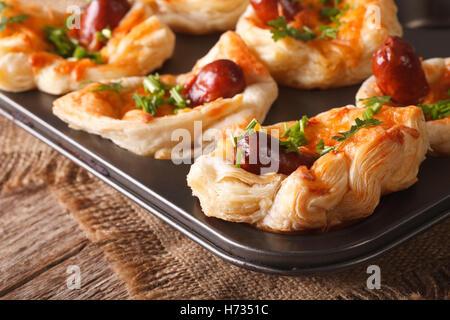 Snack-puff buns avec de la saucisse, du fromage et l'oignon dans le plat de cuisson macro horizontale. Banque D'Images