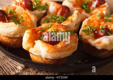 Snack-brioches de pâte feuilletée avec de la saucisse et le fromage sur un plateau de près. L'horizontale Banque D'Images
