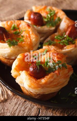 Snack-brioches de pâte feuilletée avec de la saucisse et le fromage sur une plaque verticale close-up. Banque D'Images
