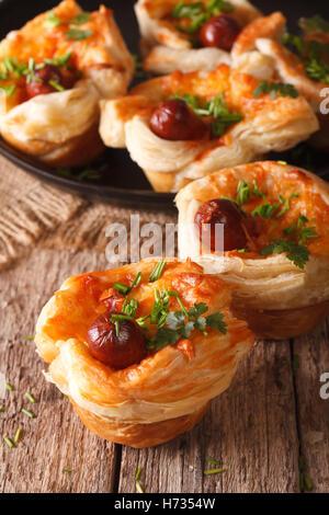 Petits pains de pâte feuilletée avec de la saucisse et le fromage sur la table verticale. Banque D'Images