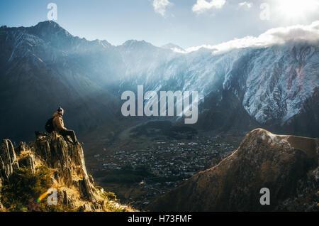Les jeunes touristes en chapeau lumineux, un pantalon noir avec un sac à dos s'asseoir sur le bord de la falaise Banque D'Images
