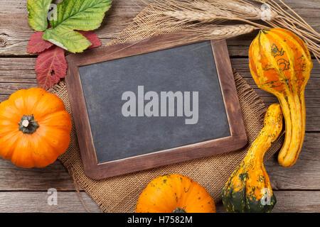 Citrouilles d'automne sur planche de bois table. Vue supérieure avec tableau pour copy space Banque D'Images