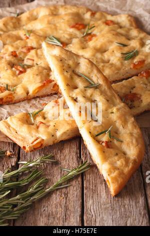Focaccia italienne traditionnelle avec Rosemary fermer vers le haut sur la table. vertical Banque D'Images