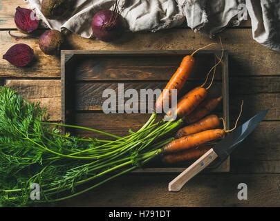 Les carottes et les betteraves fraîches dans le bac en bois sur fond rustique Banque D'Images