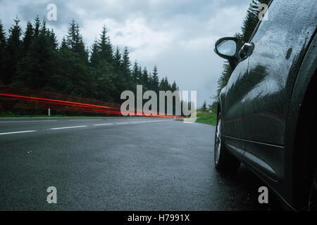 Des sentiers et des feux de véhicule automobile sur la route humide. Temps de pluie. Selective focus, une longue Banque D'Images