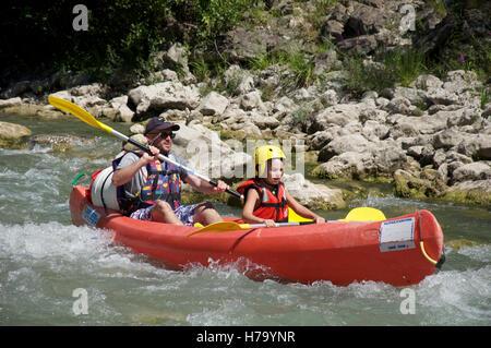 Le tourisme, les sports d'eau. Un père et son jeune fils en canoë sur les eaux à débit rapide de la Drôme. Près Banque D'Images