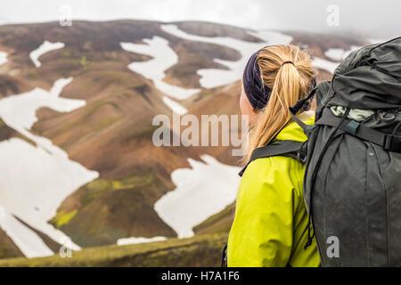 Un jeune randonneur avec vue sur les montagnes en Landmannlaugar. Banque D'Images