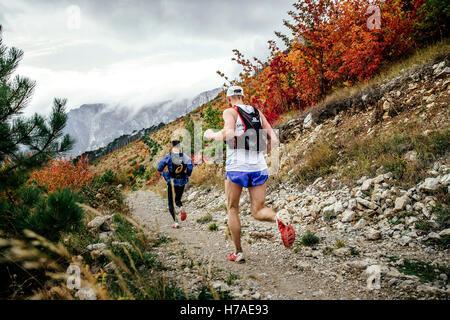 Les coureurs deux athlètes de montagne le long trail en paysage d'automne au cours de Crimée marathon de montagne Banque D'Images