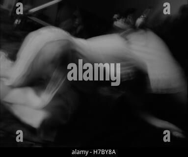 Un trouble atmosphérique image en noir et blanc d'une jeune fille portant une ancienne robe de nuit se penchant Banque D'Images
