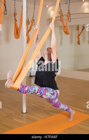 Homme ayant participé à la classe de yoga aérien femme avec instructeur, en position de yoga dans un hamac, une Banque D'Images