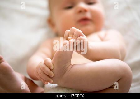 Adorable bébé s'intéresser à ses pieds Banque D'Images
