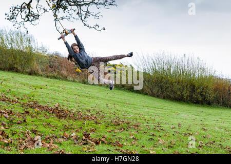 Teenage girl swinging on a rope swing en plein air modèle libération: Oui. Biens: Oui. Banque D'Images