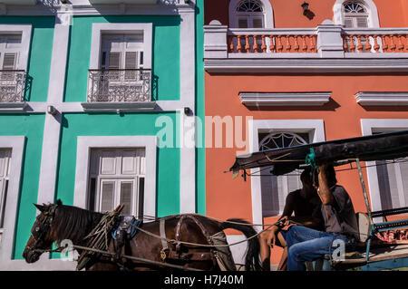 Transport de chevaux tirant en face de façade coloniale colorée