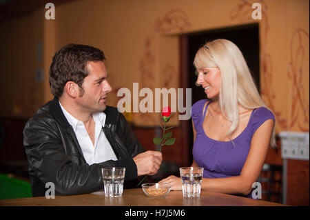 Ce jour, l'homme et la femme avec une rose rouge au bar Banque D'Images