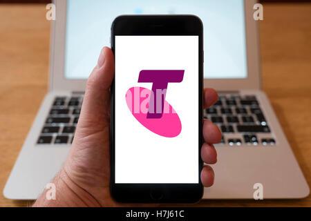 L'utilisation de l'iPhone téléphone intelligent pour afficher le logo de Telstra, est la plus grande entreprise Banque D'Images