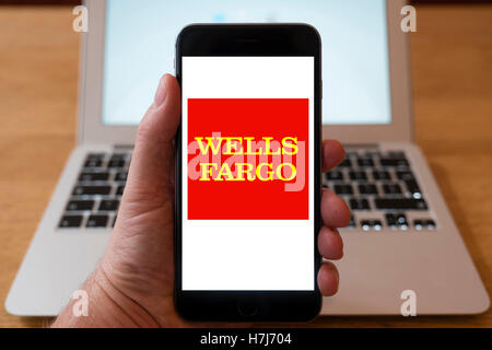À l'aide d'iPhone smartphone pour afficher le logo de la Wells Fargo , l'American International Banking and financial Banque D'Images