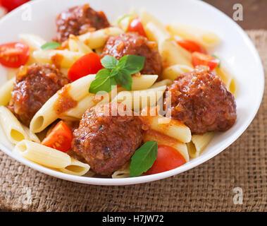 Pâtes penne avec des boulettes de viande en sauce tomate dans un bol blanc. Banque D'Images