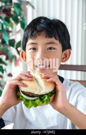 Garçon asiatique ayant un hamburger pour le déjeuner. Banque D'Images
