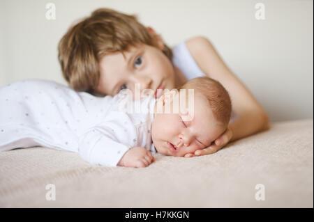 Bébé en pyjama blanc dormant sur son estomac, frère aîné hugs Banque D'Images