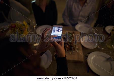 Femme photographiant la nourriture avec téléphone appareil photo au tableau sombre Banque D'Images