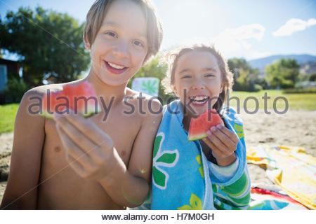 Portrait of smiling brother and sister eating watermelon on sunny summer beach Banque D'Images