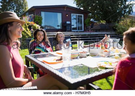 Manger en famille à table de patio d'été ensoleillé Banque D'Images