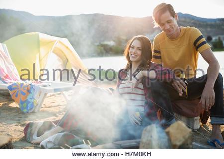 Couple et de boire de la bière au camp d'été sur la plage au bord du lac Banque D'Images