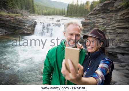Woman with camera phone selfies at waterfall Banque D'Images