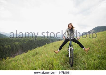 Femme ludique équitation vtt dans des zones rurales domaine Banque D'Images